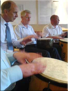 A group learning to work together whilst having fun finding out how to drum.